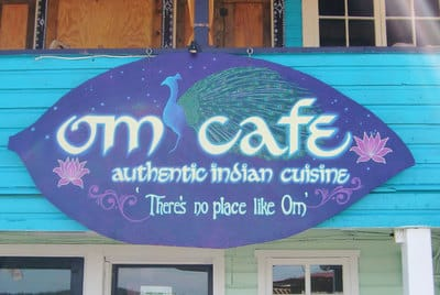 Hand painted Indian cafe sign with peacock and lotus flowers in Bocas del Toro.
