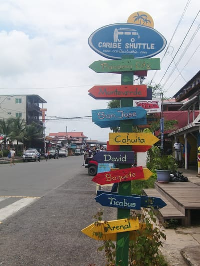 Hand painted sign with arrow pointers in Bocas del Toro.