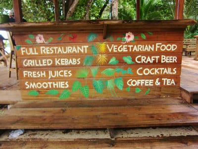 Hand painted lettering with tropical flowers and plants on beach in Bocas del Toro.