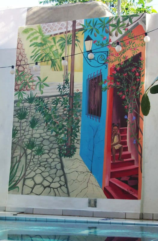 Santo Domingo mural with girl and tropical flowers in street scene.