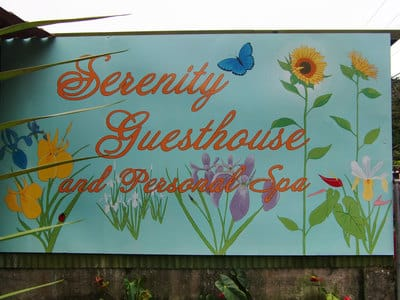 Hand painted guesthouse sign with flowers.