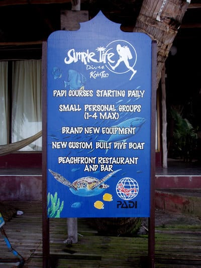 Hand painted sign with turtle, tropical fish and dive shop logos.