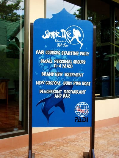 Hand painted sign with whale shark and dive shop logos.